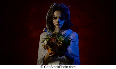 Close up of a ghost of a girl with bunch of flowers in her hands and looking at it. Young beautiful woman with art skull make-up on her face is participating in Halloween party