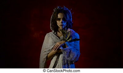 Close up of a ghost of young girl is standing with sad face and staring at the camera. Phantom of a young woman having creative Halloween skull make-up on her face. Dead bride is standing in the dark room against red background with her head covered with veil and flowers.