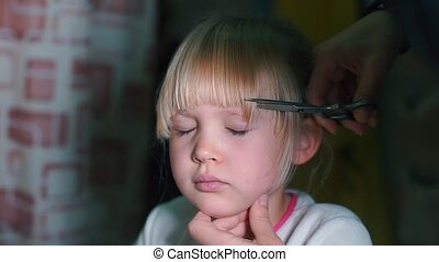 Close-up of a girl cutting hair on her head.