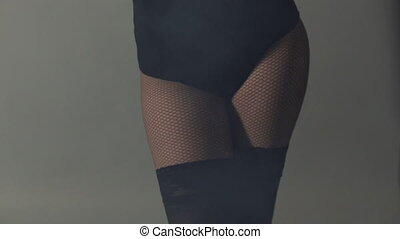 Close-up of a girl dancing and moving sexy in stockings in...