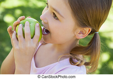 Close-up of a girl eating apple in park
