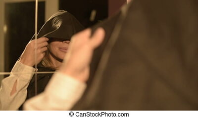 Close-up of a girl magician in front of a mirror puts on the...