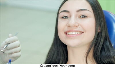 Close-up of a girl patient who teeth smile and a dentist begins inspection
