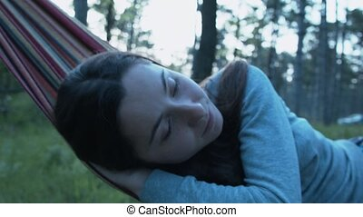 Close-up of a girl rocking on a hammock. A young woman is rocking on a hammock in the park. The portrait of a girl moving away from the camera and approaching on a hammock.