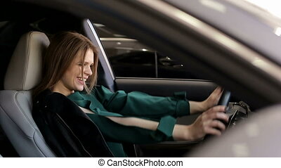 Close-up of a girl sitting in a new car behind the wheel in a car dealership.