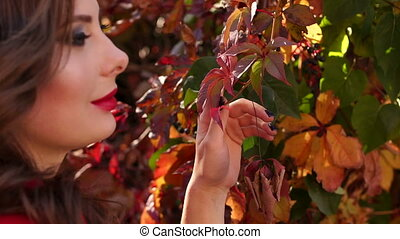 Close-up of a girl walking in autumn park on the background of autumn leaves.