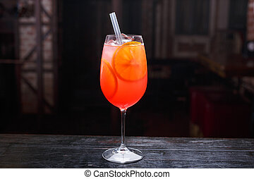 Close up of a glass of aperol spritz cocktail, standing on the bar counter, isolated on a red light background.
