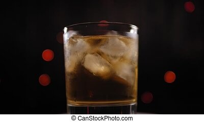 Close-up of a glass of whiskey with ice spinning on a blinking background.