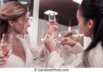 Close up of a glass with champagne in female hands -...