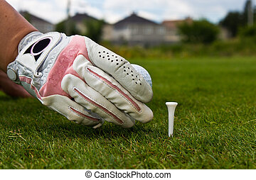 Close-up of a gloved hand of a female golfer placing golf ball o