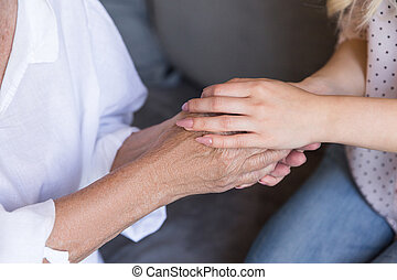 Close up of a granddaughter and grandmother holding hands
