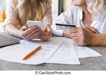 Close up of a grandmother and her granddaughter paying online