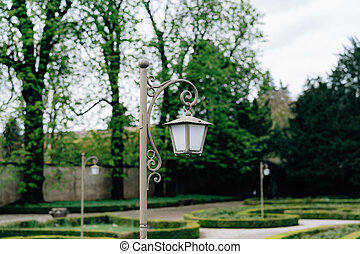 Close-up of a gray street lamp in the park on the alley.
