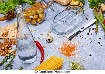 Close-up of a gray table with pasta, a bottle, red chili pepper, walnuts, olives, asparagus on a light gray background.