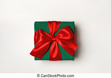 Close-up of a green box with a gift and a red ribbon on a white background