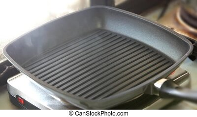 Close up of a grill pan smoking with heat while preparing to cook some food