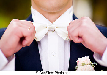 close-up of a groom aligning a bow tie on his neck
