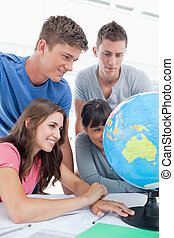 Close up of a group of students looking at the globe