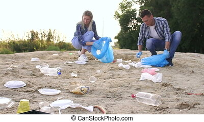 Close-up of a group of volunteers collecting plastic garbage on the beach.