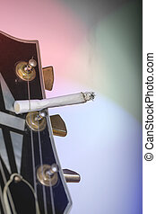 close up of a guitar headstock with burning cigarette sticking under one string.