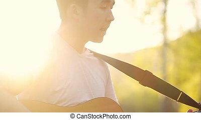 Close up of a guitar player singing and playing the guitar in the beautiful sunset slow motion
