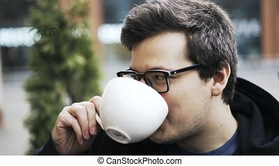 Close up of a guy in glasses drinking coffee, listening to friends and laughing