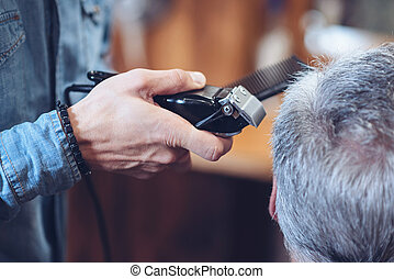Close up of a hair cutting machine being in barbers hands