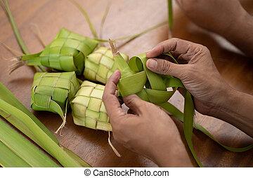 making ketupat traditional indonesian rice cake - close up...