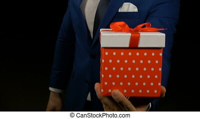 Close up of a hand of a man holding and showing gift box with red ribbon