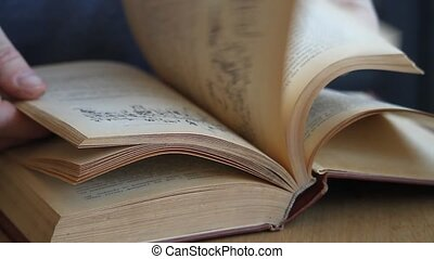 Close-up of a hand of man leafing through a book in Russian, running his fingers through the pages, studying the material