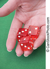 close up of a hand throwing dices on a green table