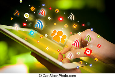 Close-up of a hand using tablet with social media icons