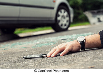 Close-up of a hand with a watch lying on the road next to a broken phone