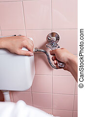 Close-up of a hands repairing toilet