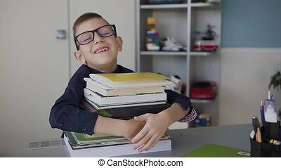 Close-up of a handsome boy who wears glasses, runs to the desk behind which he does homework and hugs his books with fun. Homework