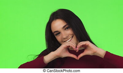 Close up of a happy beautiful woman smiling showing heart sign