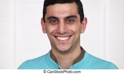 Close-up of a happy middle eastern man smiling, white...