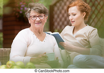 Close-up of a happy senior woman and a her young professional nurse who is reading a book during leisure time on a patio of a day care facility. Blurred background