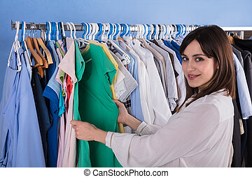 Woman Choosing Clothes On Clothes Rail