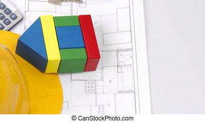 Close-up of a house plan and a key turning
