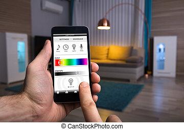 Human Hand Adjusting Electric Light Through Mobile Phone