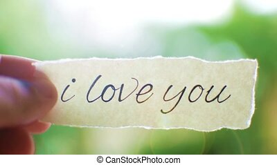 Close-up of a human hand holding love message. Bokeh effect.
