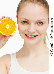Close up of a joyful woman presenting an orange