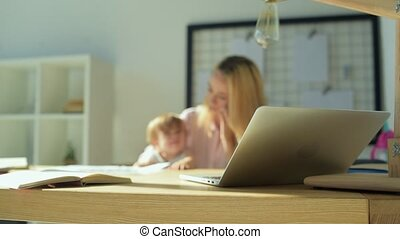 Close up of a laptop with the family in the background