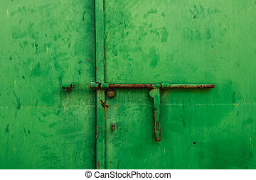 Close up of a latch on a green metal door