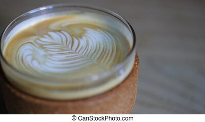 Close up of a Latte - Panning shot of a glass of latte sat...