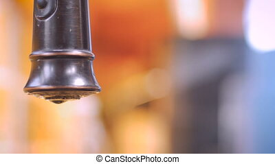 Close up of a leaking faucet with a person cleaning up in the background