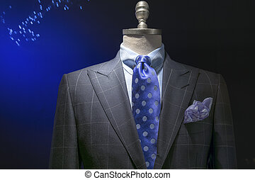 Close-up of a light gray checkered jacket with blue checkered shirt, blue polka dots tie and handkerchief on dark background. Clipping path included.