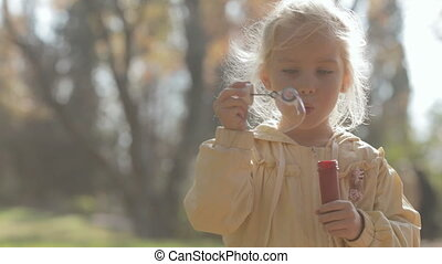 Close up of a little blonde girl blow bubbles on nature
