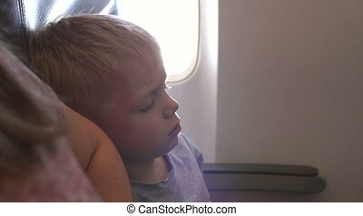 Close-up of a little boy sleeping in a airplane leaning on his mother's shoulder